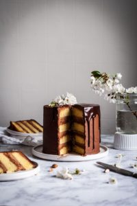 yellow marzipan layer cake with dark chocolate buttercream with slices cut out and laying…
